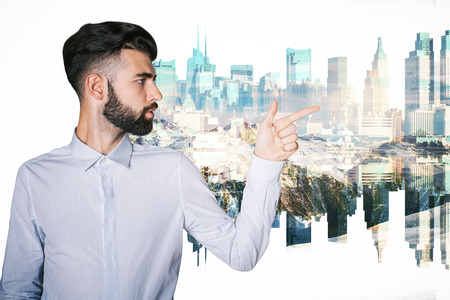 Beared young man pointing at abstract city on white backgroun
