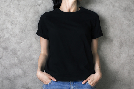 Fille en chemise noire et un jean clair sur backgroud béton. Maquette