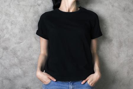 Ragazza in camicia nera pianura e jeans su backgroud calcestruzzo. Modello