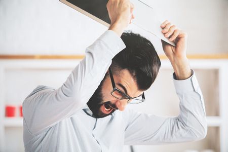 violence in the workplace: Furious man at workplace throwning his laptop. Anger issues and stress concept