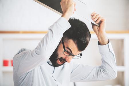 enfado: Hombre furioso en el lugar de trabajo throwning su ordenador portátil. problemas de ira y concepto de la tensión