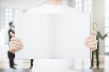 man holding book: Young man holding empty book on blurry background. Mock up
