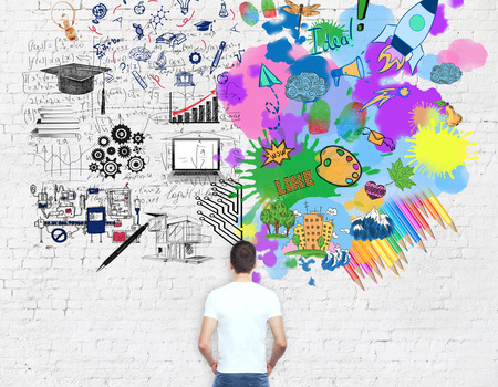 analytical: Young man looking at bright colorful sketch on brick background. Creative and analytical thinking concept