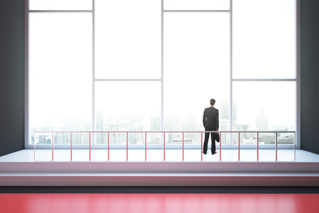 looking at view: Businessman looking out of window in interior with red floor, railing and city view. 3D Rendering Stock Photo