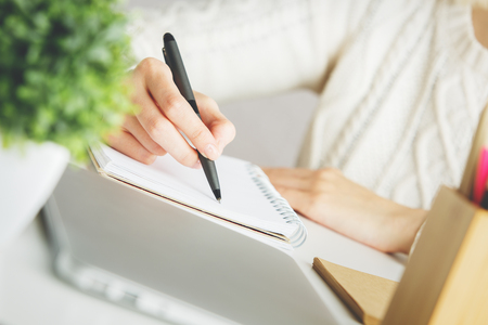 close  up: Close up of womans hand writing in spiral notepad on desktop with decorative plant
