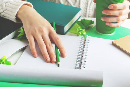 assignments: Lady holding green coffee cup and writing in spiral notepad placed on creative desktop with various items. Close up
