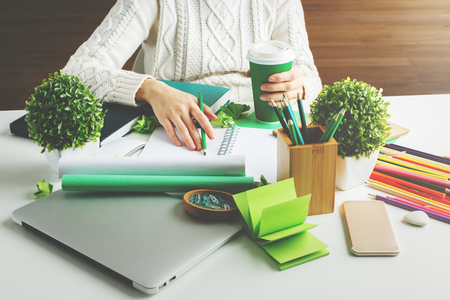 Girl hodling green coffee cup and writing in spiral notepad placed on creative desktop with various items 스톡 콘텐츠