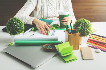 Meisje hodling groene koffiekopje en schrijven in spiraal notitieblok geplaatst op creatieve desktop met diverse artikelen Stockfoto