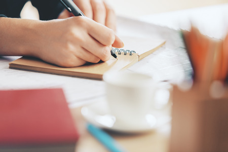 schreiben: Close up of females hands writing in spiral notepad placed on wooden desktop with coffee cup and other items Lizenzfreie Bilder