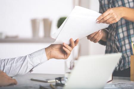 Cierre plano de raza caucásica hombre y una mujer entregando los documentos entre sí. concepto del trabajo Foto de archivo