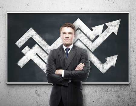 folded arms: Handsome young businessman with chart arrows on blackboard. Financial growth concept