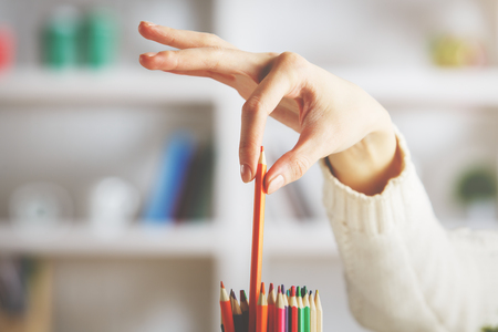 Close up of girls hand taking red pencil out of holder on blurry shelf background