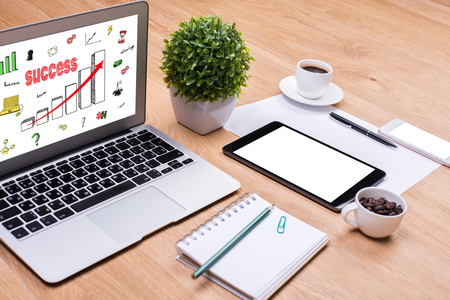 success in business: Close up of wooden office desktop with creative business sketch on laptop screen, blank tablet, coffee cup and other items. Success concept