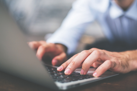 web side: Side view of male hands typing on laptop keyboard Stock Photo