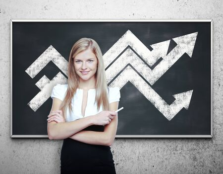 young businesswoman: Attractive young businesswoman with chart arrows on blackboard. Financial growth concept