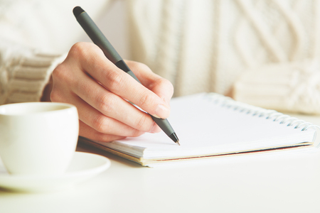 Woman writing in spiral notepad placed on bright desktop with coffee cup. Education concept Imagens