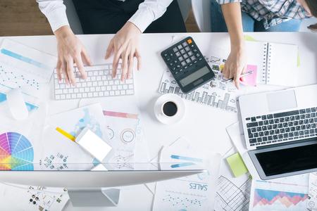 contabilidad: Equipo de dos personas que trabajan en escritorio con los informes financieros, calculadora, dispositivos electrónicos, la taza de café y otros artículos. concepto de estadísticas Foto de archivo