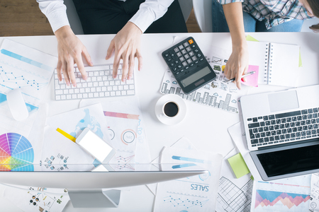 Team of two working at desk top with financial reports, calculator, electronic devices, coffee cup and other items. Accounting concept
