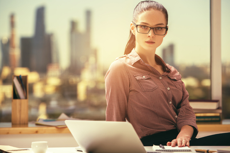 Portrait of thoughtful caucasian female at her office desktop with city view