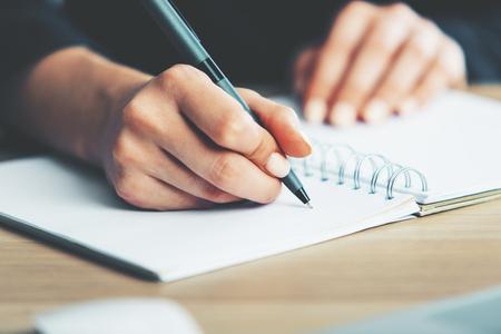 様々 なアイテムと木製のデスクトップ上に配置スパイラル メモ帳で書く女性の手のクローズ アップ