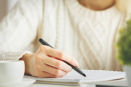 Girl writing in spiral notepad placed on bright desktop with coffee cup. Education concept 스톡 콘텐츠