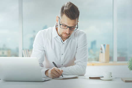 Handsome young male working on project at modern office desk