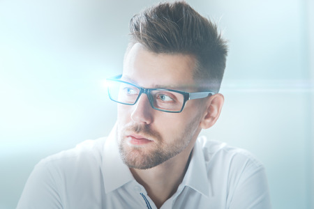 shot: Close up portrait of attractive young businessman in glasses on blurry city background Stock Photo
