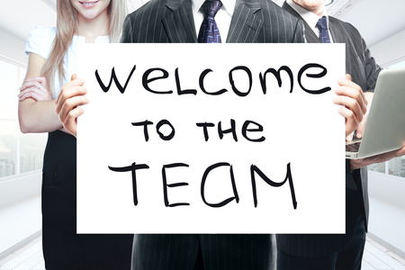 Businesspeople holding whiteboard with 'welcome to the team' text. Teamwork concept
