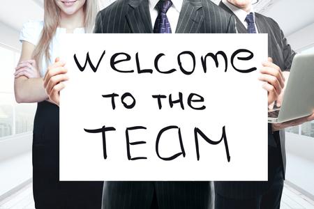 """Los empresarios que sostienen una pizarra con """"bienvenido al equipo 'texto. concepto del trabajo"""