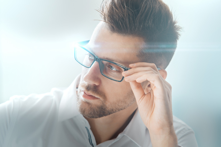 Close up portrait of attractive young man in glasses on blurry city background