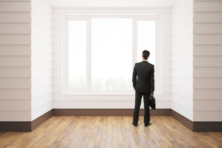 unfurnished: Businessman standing in unfurnished white room with wooden floor, city view and daylight. 3D Rendering Stock Photo