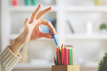 Close up of girls hand taking blue pencil out of holder on blurry shelf background
