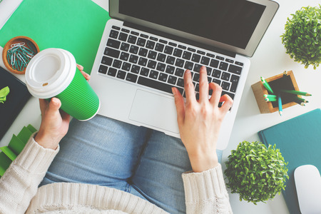 Casual woman holding coffee cup and using laptop with empty screen while sitting on white background with various items. Mock up