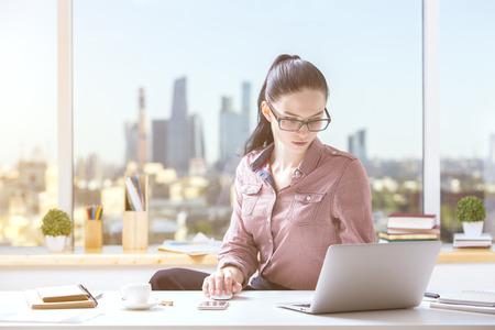 Portrait de belle fille utilisant un ordinateur portable au lieu de travail. concept de projet