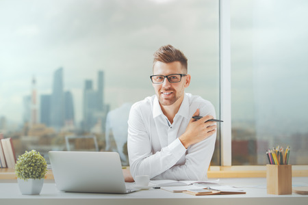 Attractive young guy working on project at modern office desk
