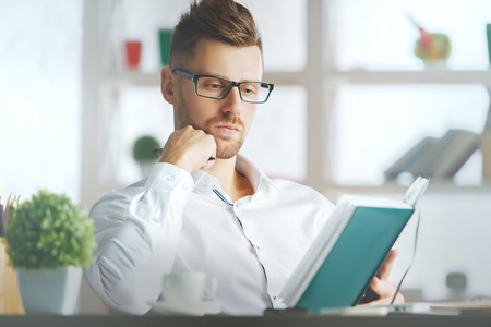 Portrait of handsome european businessman at workplace writing in hardcover organizer