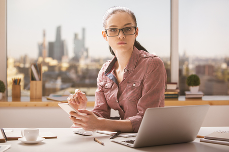 Portrait of thoughtful caucasian businesswoman at her office desktop with city view