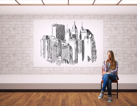 apartment: Thoughtful young woman in interior with city sketch on whiteboard Stock Photo