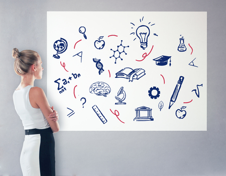 looking at view: Side view of elegant young woman looking at whiteboard with scientific drawings. Education concept