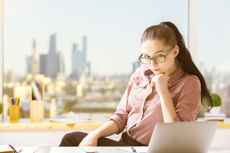 Portrait of thinking caucasian girl at her office desktop with city view Stock Photo