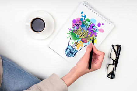 idea: Hand drawing creative sketch in spiral notepad placed on white surface with coffee cup and glasses. Business idea concept
