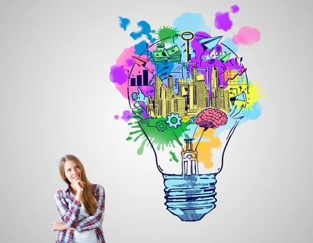 pensamiento creativo: Alegre mujer europea con el bosquejo creativo sobre fondo gris. Concepto de las ideas de negocio