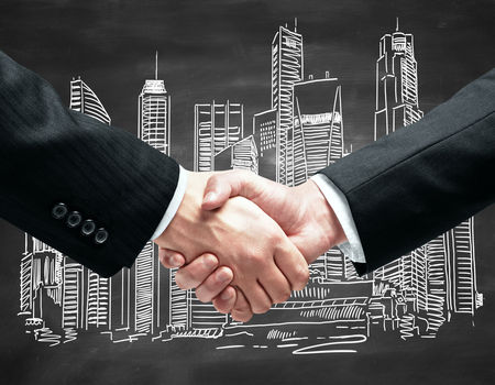 city: Close up of handshake infront of blackboard with city sketch. Partnership concept Stock Photo