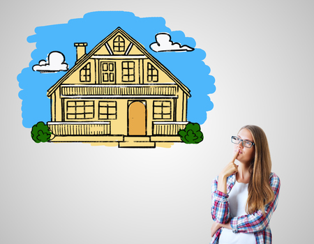 drawing a plan: Attractive caucasian girl on grey background with colorful house sketch. Real estate, mortgage and housing concept