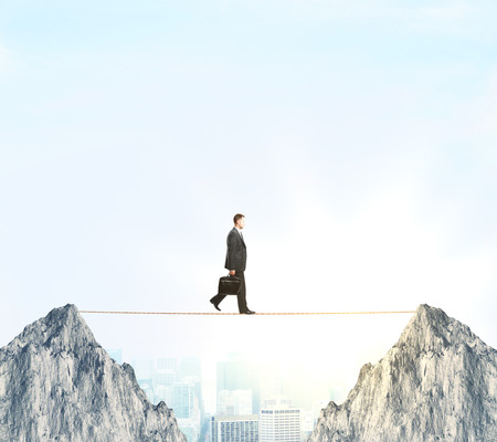 equilibrium: Side view of businessman with briefcase walking in rope between two cliffs on city and sky background. Risk balancing concept