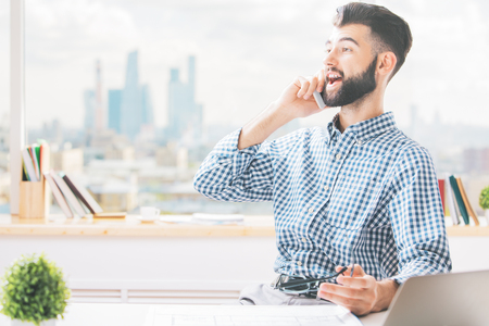 1: Cheerful caucasian guy sitting at workplace and talking on cellular phone