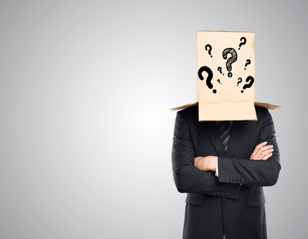 masquerader: Businessman with folded arms and cardboard box with question marks covering head on grey background. Confusion concept Stock Photo