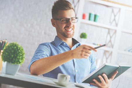 hombre escribiendo: Retrato de hombre de negocios caucásico atractivo en el lugar de trabajo escribiendo en organizador de tapa dura