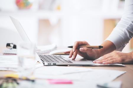 ラップトップ コンピューターを使用して実業家の手の側面図が乱雑なオフィスのデスクトップ上に配置 写真素材