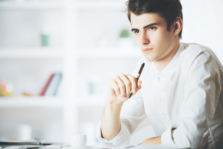 authors: Portrait of young man at workpace writing in notepad